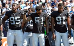 Oakland Raiders outside linebacker Bruce Irvin (51) raises a fist during the playing of the national anthem before an NFL football game against the Tennessee Titans Sunday, Sept. 25, 2016, in Nashville, Tenn. At left is defensive end Jihad Ward (95) and at right is linebacker Shilique Calhoun (91). (AP Photo/Mark Zaleski)
