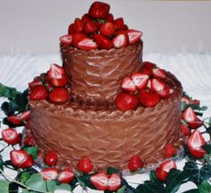 2-tier grooms cake with buttercream icing in wave design and fresh strawberries on cake.