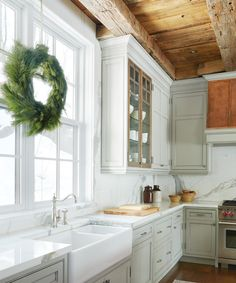 Hanging above the farmhouse sink, a simple wreath adds a hint of holiday spirit in the kitchen.