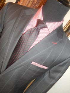 FROM THE STYLES BY KUTTY (SBK) DESIGN CENTER: CHARCOAL GREY WINDOWPANE SUPER120 - 100% WOOL CUSTOM-MADE SUIT. 100% COTTON, RED BENGAL STRIPE CUSTOM-MADE SHIRT AND MATCHING POCKET SQUARE. ALL CUSTOM-MADE FROM SBK. CHARCOAL GREY TIE W/ RED CIRCLES FROM THE SBK COLLECTION.