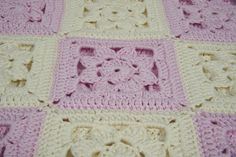 """""""Rose Marzipan"""" is a handmade baby blanket. The soft bamboo cotton yarn is crocheted in white and pink flowers motifs reminding of a box of marzipans. Let your baby feel its soft embrace."""