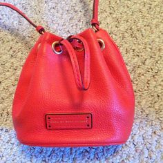 """Orange bucket crossbody bag Orange bucket bag by Marc by Marc Jacobs. It's called the """"too hot too handle"""" small bag. Shoulder strap is adjustable. Drawstring close. It can fit wallet, keys, makeup, and other essentials. In pristine, like new condition. I bought this from another posher because I thought I could use a small bag but I hoard too many things in my bag! It's super cute. Color most like last picture. Authentic. Open to offers. Marc by Marc Jacobs Bags Crossbody Bags"""