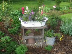 Old enamel pan on a wooden stand is centered in the garden bed