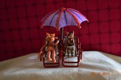 Two kitties sitting under a beach umbrella in beach chairs. $25.00, via Etsy.