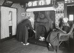 Marrigje Hagen-van Engbrink en Aaltje Hagen-Bonhof uit Nunspeet bij de haard. Beiden dragen de streekdracht van de Noordwest-Veluwe. Ze dragen hun dagelijkse kleding. Boven het open vuur hangt een ketel. Links is een bedstede. 1918-1941 vanAgtmaal #Gelderland #Veluwe #Nunspeet #oudedracht