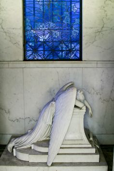"4' tall Chapman Hyams weeping angel~Two blue stained-glass windows on either side of the mausoleum cast light onto the marble statue of ""Grief"" –an angel weeping. New Orleans"