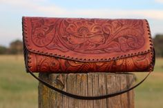 Hand tooled and beautifully accented in brown leather, the floral pattern is distinctively stunning and is a standout.  Lined with a soft swede, this Juan Antonio handbag is large enough for your necessary items and the perfect size to not weigh you down. It can be a wallet, clutch bag or a shoulder bag.   The strap is removable or can be tucked away in the handbag for easy access. (http://www.acowgirlspromise.com/juan-antonio-saddle-brown-tooled-leather-clutch-handbag/)
