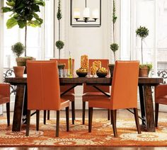 Orange Chair For Cheerful Home Decoration: Pretty Dining Room Decoration With Brown Wood Rectangular Dining Table Designed With Iron Trestle Complete With Orange Chairs On The Wooden Legs Combine With Vintage Orange Rug On The Brown Wood Laminate Floor ~ evenion.net Furniture Inspiration