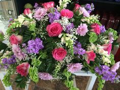 Hot pink roses, lavender cremones, lavender stock, light pink snapdragons & bells of Ireland casket spray by Donna Jeffries