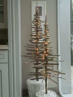 Driftwood christmas trees.  Great idea using a white basic filled with white pebbles as a base.