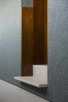 Protruding stone cantilever step, stone shadow gap wall cladding, timber lining, bronze cladding