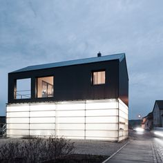 This black house is raised up over a translucent base where the client's truck can be stored