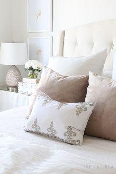 Velvet throw pillows | Tall tufted headboard | Frames above nightstand