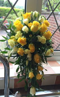 Yellow penny lane roses, spray roses, spray carnations, sea holly and lisianthus - shower bouquet