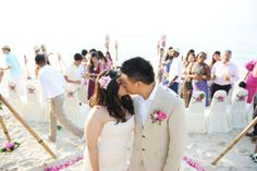 Include your guests in the shot of your first kiss as bride and groom. Photograph by Khun Aez