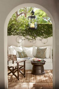I LOVE everything about this...the archway, latern, tile, rug, sofa, pillows, greenery on the wall.  Unfortunately, I don't think I have the skills or patience to keep a white sofa clean outdoors!