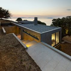 House+in+Kea+is+a+concrete+residence+built++around+oak+trees+on+a+Greek+isle