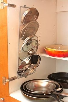 Magazine rack inside cabinet as pot lid holder. Genius....lids are such a pain!
