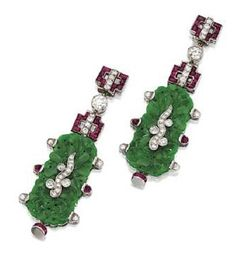 PAIR OF CARVED JADE, RUBY AND DIAMOND PENDANT-EARRINGS, CIRCA 1925. The pendants formed of carved jade plaques applied with diamond-set scroll motifs, surmounted and bordered by numerous cabochon and calibré-cut rubies and old European-cut and single-cut diamonds, the total diamond weight approximately 1.50 carats, mounted in platinum.