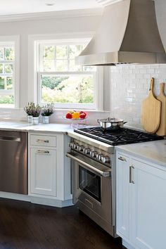 Under a stainless steel French hood, a stainless steel oven range sits against white subway backsplash tiles between angled white shaker cabinets donning nickel pulls and a White Macauba Quartz countertop fixed beneath windows and above a stainless steel dishwasher.