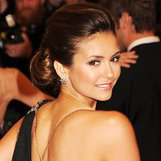 Nina Dobrev's Elegant Chignon  Even though Nina Dobrev's polished style embodies all the elements of a classic updo, it manages to maintain a touchable appearance. When going for a similar look, keep styling products down to the essentials to keep your strands soft, but add extra volume at the crown to keep it from looking like a prom updo.