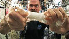 Commander Chris Hatfield wringing out a Water Soaked Washcloth in Space