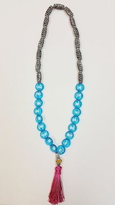 Bright blue and pink tassel necklace handmade by artists with intellectual and developmental disabilities. 100% of purchase goes to charity Evergreen Life Services charity with 50% of each purchase going straight to the individual who made the item.  We hope to grow our program so our artists can continue to make more work and feel empowered in the process.  Each item sold comes with a picture of the artist who made the item and a thank you for supporting our organization. ...