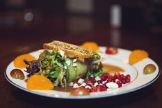 Fresh plated salad with grapes, mandarin oranges, & pomegranate ornamenting wrapped greens tied with a cucumber strip | EOL Photography | villasiena.cc