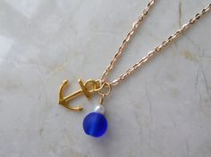 Hey, I found this really awesome Etsy listing at http://www.etsy.com/listing/153562578/gold-anchor-and-blue-sea-glass-necklace