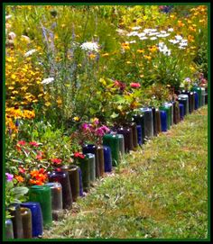 """10 ways to upcycle glass bottles and jars from """"a cultivated nest"""". Will be making a wine bottle border around the bottle tree garden. Flower Bed Borders, Flower Beds, Diy Flower, Recycled Glass Bottles, Bottles And Jars, Beer Bottles, Empty Bottles, Glass Jars, Reuse Bottles"""