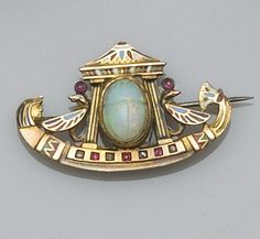 An enamelled and gem set Egyptian Revival brooch  Centred with a carved opal scarab, within a mount composed of Ancient Egyptian motifs including, a temple, a palmette, birds, and a pharaoh head, decorated with polychrome enamel and set with mixed-cut rubies and rose-cut diamonds, engraved detail verso, together with red stone set floral spray brooch suspending a pendant watch.