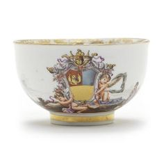 A Meissen armorial teabowl from the Foscari service, circa 1740 Painted with the coat-of-arms supported by two putti, in a continuous landscape including kauffahrtei figures and boats, the centre with a landscape panel in puce and a gilt foliate scrollwork border, 7.6cm diam, crossed swords mark in underglaze blue beneath three gold dots. This service was probably supplied to Francesco Foscari (1704-1790), a historian, lawyer and diplomat who served as envoy to Pope Benedict XIV.