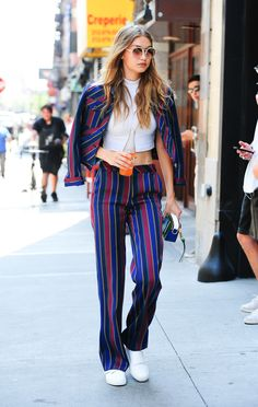 Gigi Hadid out in NYC wearing a white cropped turtle neck, a blue and red striped jacket and slacks, and white sneakers.