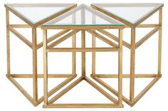 We love arranging these triangular side tables to form a fun puzzle-like surface. Framed in iron, each is topped with a layer of gleaming gold-leaf and inset glass.