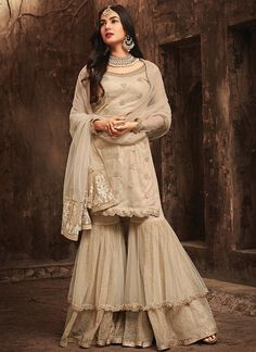 Sonal chauhan beige partywear sharara suit online which is crafted from net fabric with exclusive zari embroidery and stone work. This stunning designer sharara suit comes with sanotinne bottom santoon inner and chiffon dupatta. Sharara Designs, Kurti Designs Party Wear, Party Wear Indian Dresses, Indian Gowns, Pakistani Dresses, Pakistani Suits, Indian Designer Outfits, Indian Outfits, Designer Dresses