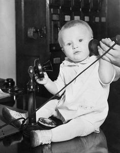 A baby found under a bed at the Stevens Hotel, Chicago, Illinois was photographed with a telephone to illustrate the many phone calls from people wanting to give him a home. 1930.