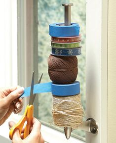 Do you keep all your tape, twine and ribbon spools in a drawer? That can look messy, waste a lot of space and make it hard to find things. Try this great organizing idea. Screw a paper towel holder to the window trim in your craft room.