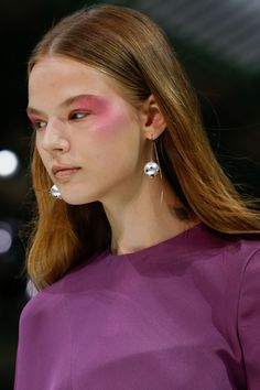 """Pat McGrath swirled fuchsia blush along the cheekbones and at the temples for a bold take on blush """"draping"""", finishing with highlighter for an iridescent effect."""