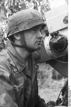 A Fallschirmjäger looks through the reflector sight of the Flakvisier 40 gunsight on a FlaK 38 anti-aircraft gun (1944), one of the more sophisticated sights at the time / France 1944
