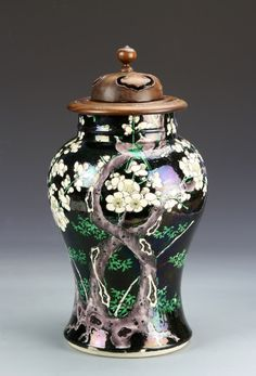 China, 19th C., Famille Noir jar, with bulbous high should, flared base, tree and flower motifs, and carved wood cover. Height 13 1/2 in.