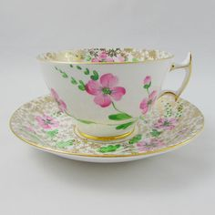 Vintage Art Deco style tea cup and saucer made by Phoenix. Covered in gold chintz with hand painted pink flowers. Gold trimming on cup and saucer edges. Excellent condition (see photos). Markings read: Phoenix Bone China T.F & S. Ltd Made in England Please bear in mind that these are
