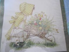 See Sally Sew-Patterns For Less - Holly Hobbie Wheelbarrow of Flowers Cross Stitch Bucilla 43783 Needlepoint Kit, $21.99 (http://stores.seesallysew.com/holly-hobbie-wheelbarrow-of-flowers-cross-stitch-bucilla-43783-needlepoint-kit/)