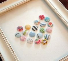 """Baby Heart Shadow Box - made from old baby clothes wrapped onto buttons.  I think I'll try this for her first birthday, but make an """"E"""" instead of a heart (even though the heart IS super sweet)...that way, each (future) baby gets one with their own initial on their 1st birthday."""