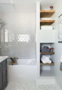 An off-white small bathroom features inserted wooden floating shelves flanked between the alcove bathtub-and-shower combo and the bathroom's white walls.Photo by Carriage Lane Design-Build Inc.