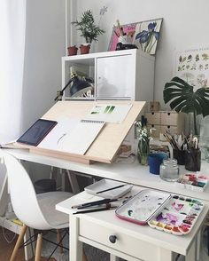 Lovely workspace for an art desk in the home office / art studio space. Desktop easel / drafting table surface plus cabinets and drawers to keep art supplies.