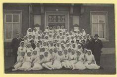 Hoofddorp 1917 Een grote groep verpleegsters in witte uniformen , samen met een paar mannen, bijeen voor de ingang van het raadhuis ter gelegenheid van de opening van het Witte Kruisgebouw.