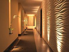 A iluminação ressalta a textura da parede e acompanha todo o corredor..