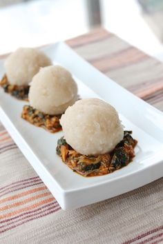 A popular Nigerian delicacy, Eba (cassava flakes) served over a bed of spicy seafood Efo Riro (spinach soup).