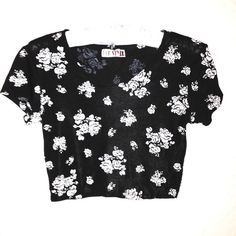 """90's Vintage Floral Crop Top True 1990's vintage! Super stretchy cropped black top with white floral prints. By Pop Style. No size label but measures as a small, could easily stretch to medium. Feels like a polyester/spandex blend. Chest measures 32-44"""". Length 15"""". Good pre-owned condition with no holes, rips, or stains.  KWs: 90s, feminine grunge, gothic, goth, revival, tumblr, edgy Vintage Tops Crop Tops"""
