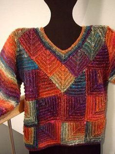 """From the designer's website: """"Eye-catching diagonal lines in mitered squares flatter your figure as the framed V-neck draws attention upward. It's great fun to knit, too!"""
